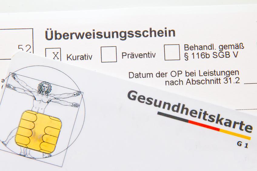 Illustration: Eine Gesundheitskarte liegt auf einem Überweisungsschein.